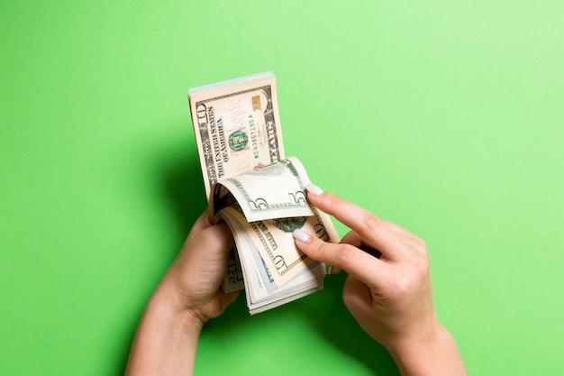 Widok z góry kobiece ręce liczenia pieniędzy. pięć i dziesięć banknotów dolarowych. koncepcja wynagrodzenia. koncepcja łapówki