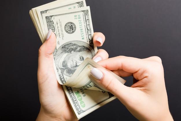 Widok z góry kobiece ręce liczenia pieniędzy. sto dolarowych banknotów na kolorowym tle. koncepcja wynagrodzenia. koncepcja łapówki