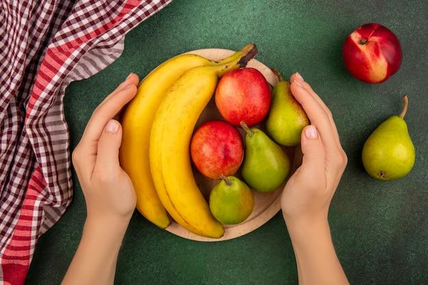 Widok z góry kobiece ręce trzymając deskę do krojenia z owocami na to jak brzoskwinia gruszka banan z kratę szmatką na zielonym tle