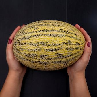 Widok z góry kobiece ręce trzymając świeży i dojrzały melon kantalupa na czarno