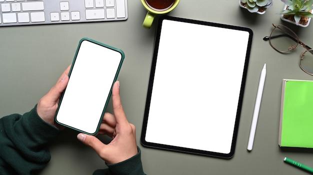 Widok z góry kobiece ręce trzymając telefon komórkowy i makiety cyfrowego tabletu na zielonym stole. pusty ekran dla wiadomości tekstowych lub treści informacyjnych.