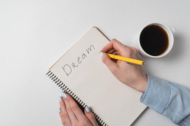 Widok z góry kobiece ręce z notebooka i filiżankę kawy. odręczny napis dream