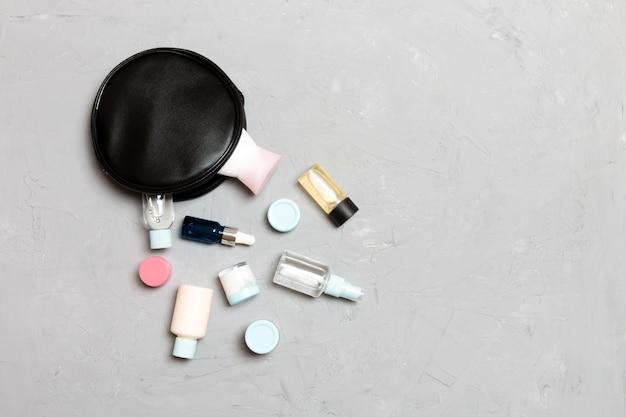 Widok z góry kobiece torby kosmetyczne z porzuconych produktów kosmetycznych na cemencie