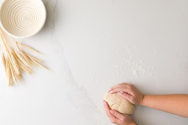 Widok z góry kobiecej dłoni formowania ciasta chlebowego w marmurowym stole z pustą miską chleba i pszenicy z miejscem na tekst