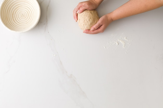 Widok z góry kobiecej dłoni formowania ciasta chlebowego w marmurowym stole z pustą miską chleba z miejscem na tekst