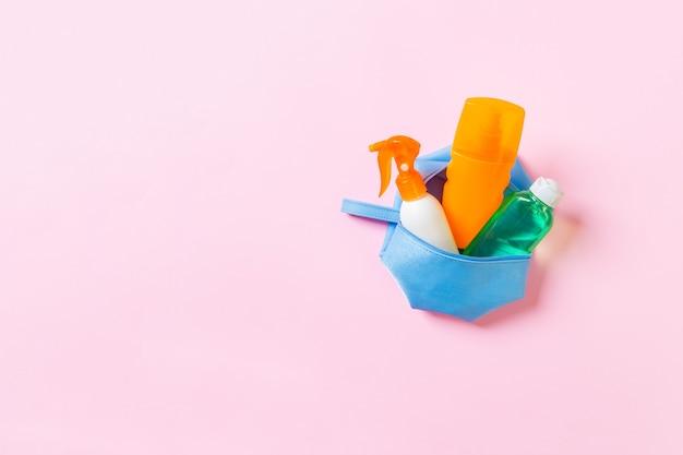 Widok z góry kobiecej kosmetyczki pełnej kremu do opalania w sprayu, sunsreen, kremu przeciwsłonecznego i balsamu do ciała oraz kremu spf na różowym tle z miejsca na kopię. bezpośrednio powyżej. koncepcja jasne lato.