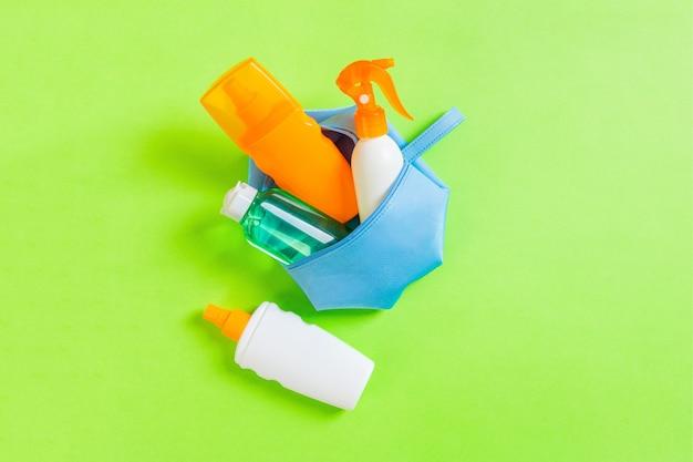 Widok z góry kobiecej kosmetyczki pełnej kremu do opalania w sprayu, sunsreen, kremu przeciwsłonecznego i balsamu do ciała oraz kremu spf na zielonym tle z miejsca na kopię. bezpośrednio powyżej. koncepcja jasne lato.