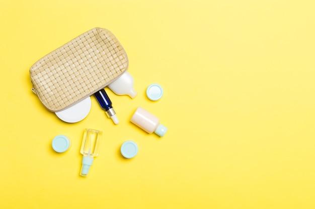 Widok z góry kobiecej kosmetyczki z porzuconymi produktami kosmetycznymi na żółtym tle. koncepcja pielęgnacji ciała z miejscem na kopię