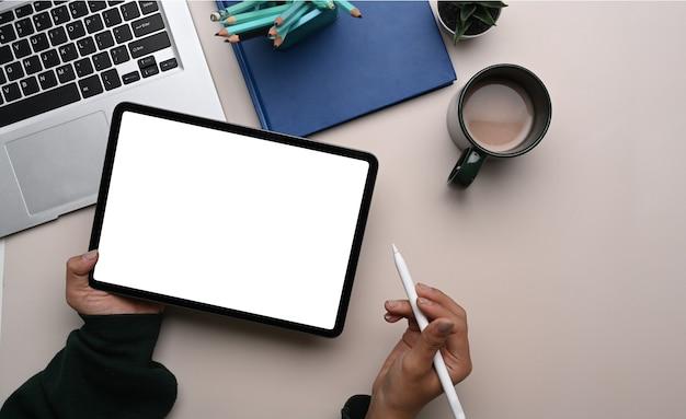 Widok z góry kobiecej ręki projektanta trzymającej cyfrowy tablet z pustym ekranem i rysikiem w jej obszarze roboczym.