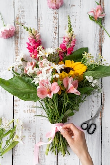 Widok z góry kobiecej ręki przygotowującej bukiet kwiatów