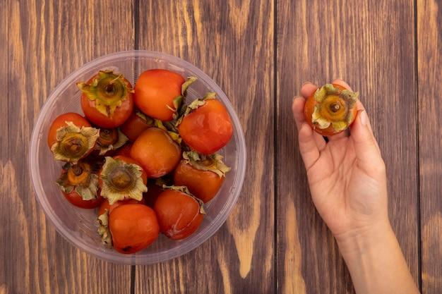 Widok z góry kobiecej ręki trzymającej dojrzałą miękką i soczystą persymonę z persimmons na przezroczystej plastikowej misce na drewnianej ścianie