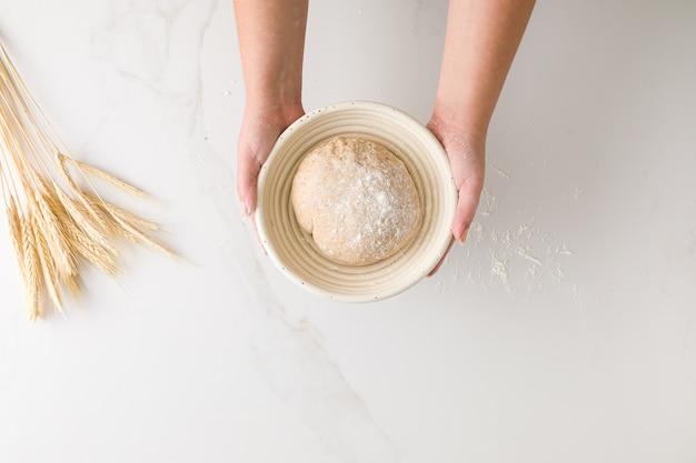 Widok z góry kobiecej ręki trzymającej odpoczywające ciasto chlebowe w misce chleba w marmurowym stole z pszenicy i mąki z miejscem na tekst