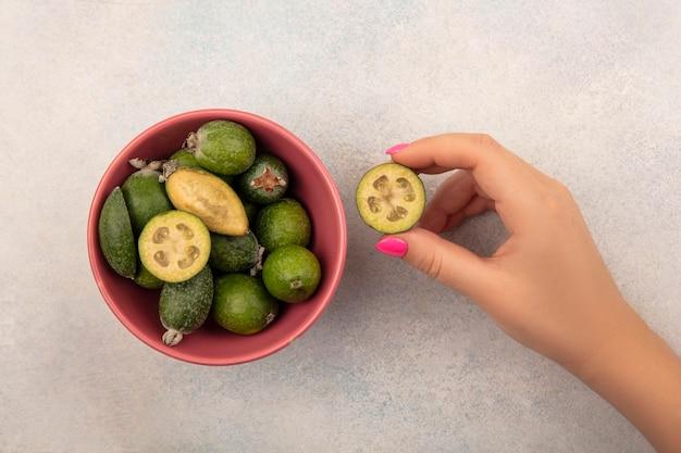 Widok z góry kobiecej ręki trzymającej słodką połowę feijoa z feijoas na misce na szarej ścianie