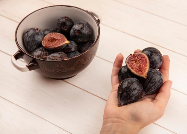 Widok z góry kobiecej ręki trzymającej słodkie czarne figi misyjne na białej powierzchni drewnianej