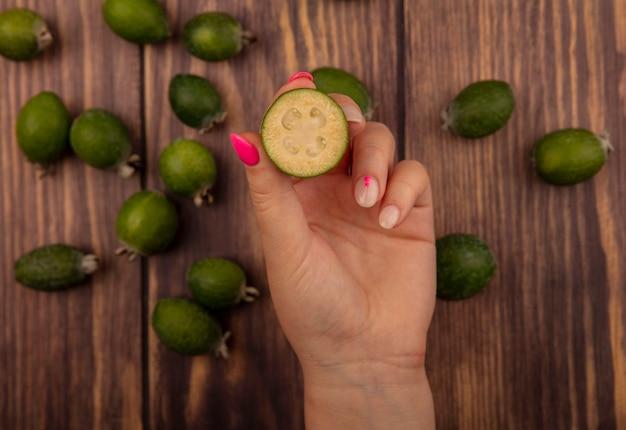 Widok z góry kobiecej ręki trzymającej surowe świeże feijoa z feijoas na białym tle na drewnianej powierzchni