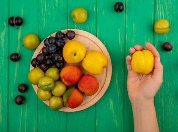 Widok z góry kobiecej ręki trzymającej żółtą brzoskwinię ze świeżymi owocami, takimi jak brzoskwinie, zielone śliwki wiśniowe na drewnianej desce kuchennej na zielonym tle
