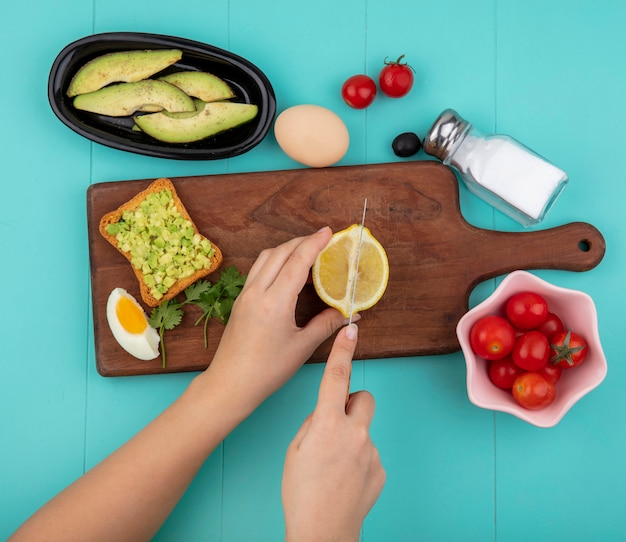 Widok z góry kobiecych rąk cięcia cytryny na plasterki na drewnianej desce kuchennej z pomidorami pół jaja plastry awokado na miskę na niebiesko
