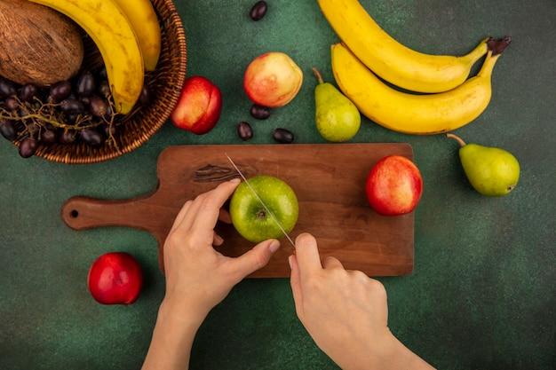Widok z góry kobiecych rąk cięcia jabłka nożem na deska do krojenia i banan, gruszka, orzech kokosowy, winogrono, brzoskwinia na zielonym tle