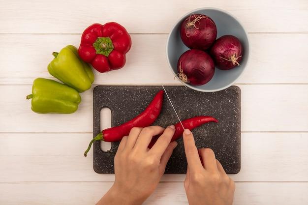 Widok z góry kobiecych rąk cięcia papryczki chili na czarnej desce kuchennej z nożem na białej drewnianej ścianie