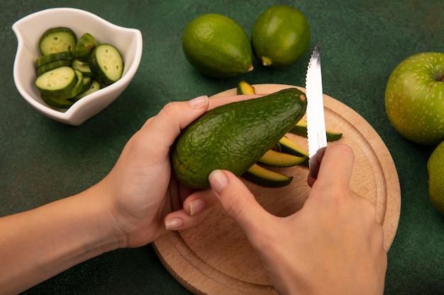 Widok z góry kobiecych rąk tnących jasnozielone awokado nożem na drewnianej desce kuchennej z limonkami i zielonymi jabłkami odizolowanymi na zielonej ścianie