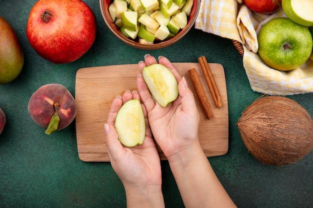 Widok z góry kobiecych rąk trzymających jabłka nad drewnianą deską kuchenną z laskami cynamonu i kokosem na zielono
