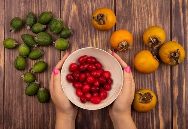 Widok z góry kobiecych rąk trzymających miskę dereń ze świeżym persimmon i feijoas na białym tle na drewnianym tle