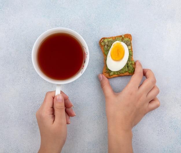 Widok z góry kobiecych rąk trzymających w jednej ręce plastry awokado na chleb, az drugiej strony acup herbaty na białym tle
