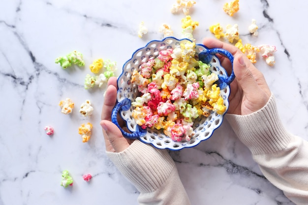 Widok z góry kobiet ręki trzymającej miskę kolorowego popcornu.