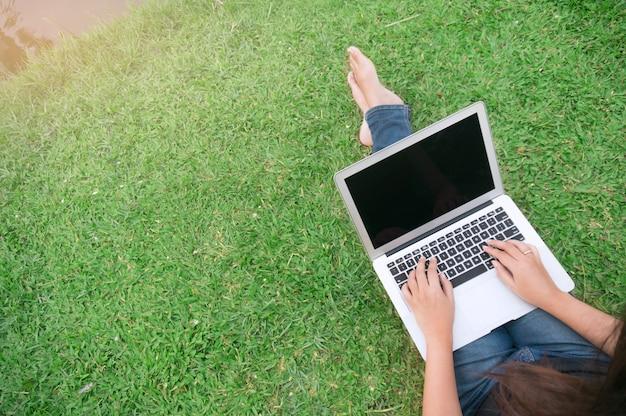 Widok z góry kobieta siedzi w parku na zielonej trawie z laptopem, studentka studiuje na świeżym powietrzu. skopiuj miejsce na tekst.