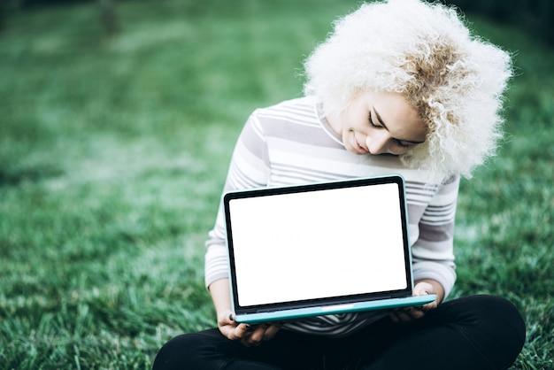 Widok z góry kobieta siedzi w parku na zielonej trawie z laptopem, studentka studiuje na świeżym powietrzu. skopiuj miejsce na tekst