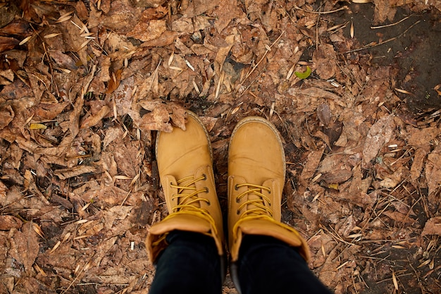 Widok z góry kobieta stojąca z butami górskimi na jesiennych liściach i drewnie