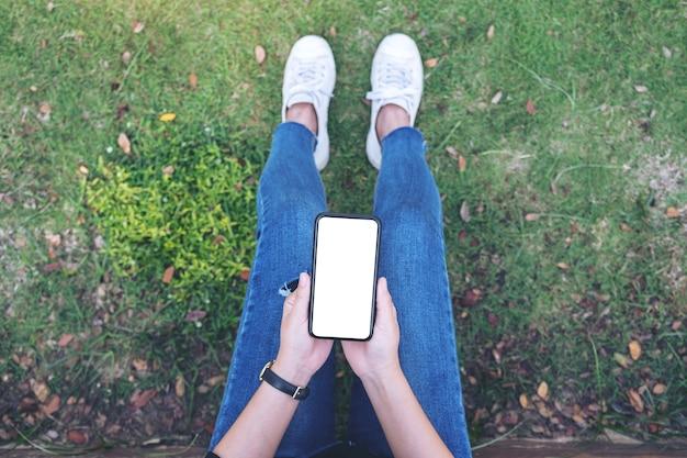 Widok z góry kobieta trzyma czarny telefon komórkowy z pustym białym ekranem siedząc w parku