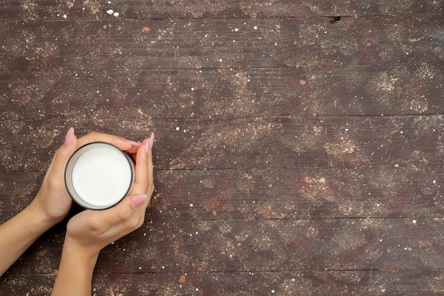 Widok z góry kobieta trzyma szkło ze świeżym zimnym mlekiem na brązowym