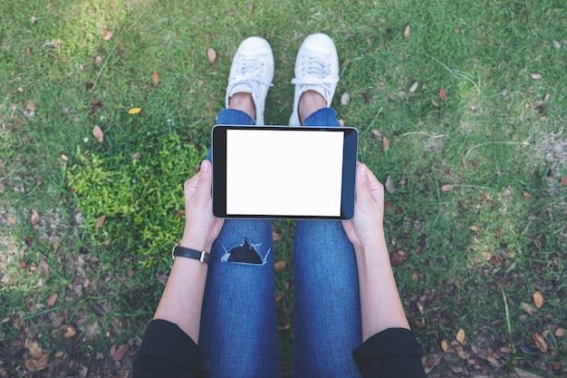 Widok z góry kobieta trzymając i używając czarny tablet pc z pustym białym ekranem poziomo, siedząc na trawie