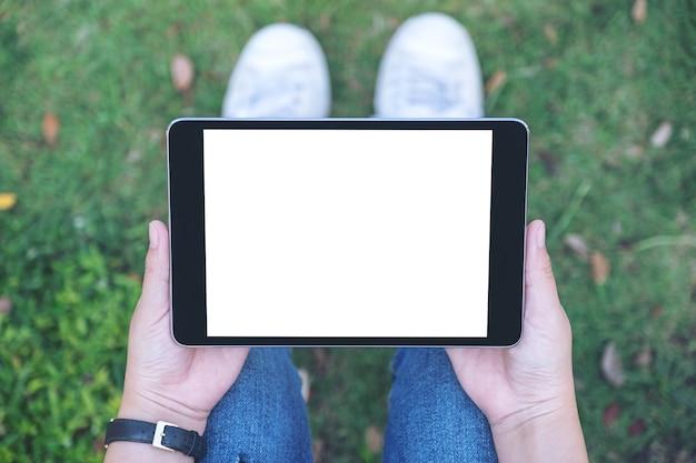 Widok z góry kobieta trzymając i używając czarny tablet pc z pustym białym ekranem poziomo, siedząc w parku