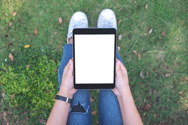Widok z góry kobieta trzymając i używając czarny tablet pc z pustym białym ekranem, siedząc na trawie