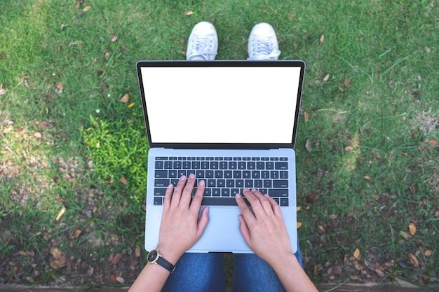 Widok z góry kobieta używając i wpisując na laptopie z pustym białym ekranem, siedząc na trawie