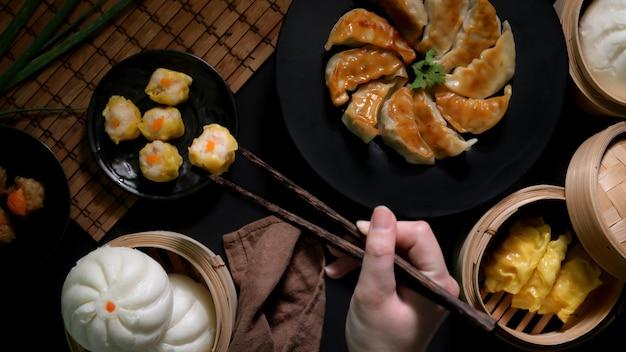 Widok z góry kobiety jedzenie dim sum z kluskami, bułkami i gyoza w chińskiej restauracji