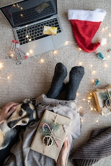 Widok z góry kobiety na zakupy online w święta bożego narodzenia, trzymając laptopa i kartę kredytową