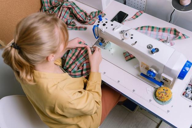 Widok z góry kobiety pracującej z maszyną do szycia w jej warsztacie, selektywne focus