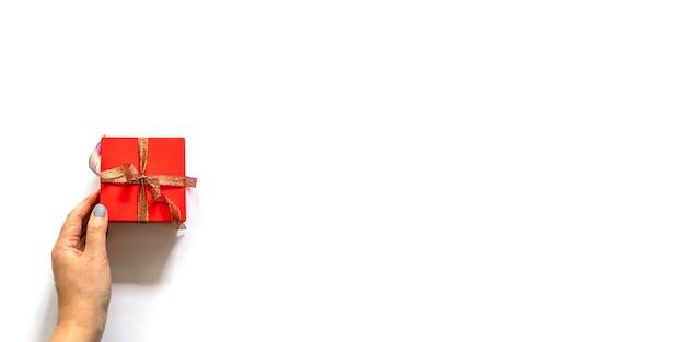 Widok z góry kobiety ręce trzyma prezent owinięty i ozdobiony kokardą na szaro