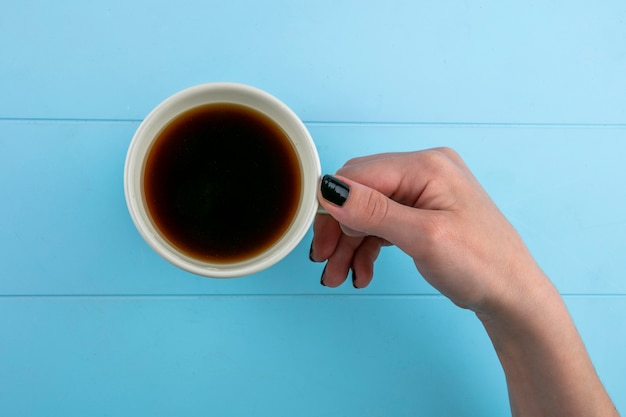 Widok z góry kobiety ręce trzymając filiżankę herbaty na niebieskim tle