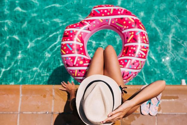 Widok z góry kobiety relaksującej w basenie z różowymi pączkami w gorący słoneczny dzień letnie wakacje idylliczne cieszy się opalenizną kobieta w bikini i kapeluszu wakacje i letni styl życia