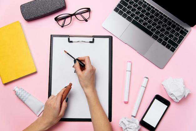 Widok z góry kobiety różowe biurko z laptopem, telefon z białym ekranem, okulary, szminka, krem i zmięte kulki papieru. żeńska ręka pisze pomadce na białym prześcieradle papierowy tło.