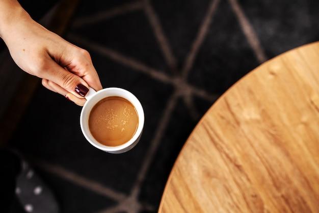 Widok z góry kobiety trzymającej świeżą poranną kawę arabica ze stołu.