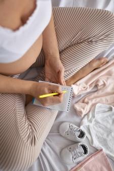 Widok z góry kobiety w ciąży w łóżku przygotowującej ubrania dla dzieci w domu i piszącej listę rzeczy do zrobienia i rzeczy w zeszycie, koncepcja ciąży i porodu