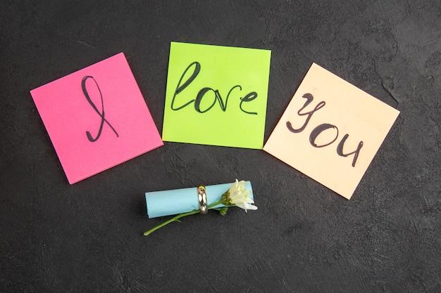 Widok z góry kocham cię napisane na karteczkach samoprzylepnych pierścionek zaręczynowy kwiat zwinięty karteczka samoprzylepna na ciemnym tle