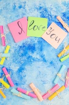Widok z góry kocham cię napisane na karteczkach samoprzylepnych przewiń papiery życzeń na niebieskim tle kopiuj miejsce