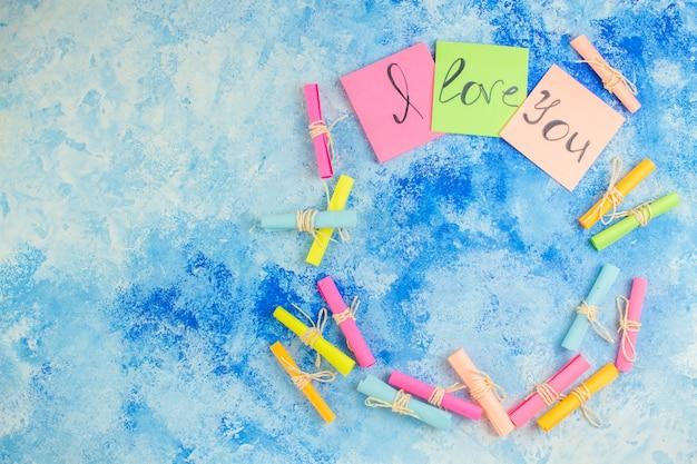Widok z góry kocham cię napisane na karteczkach samoprzylepnych przewiń papiery życzeń na niebieskim tle z miejscem na kopię