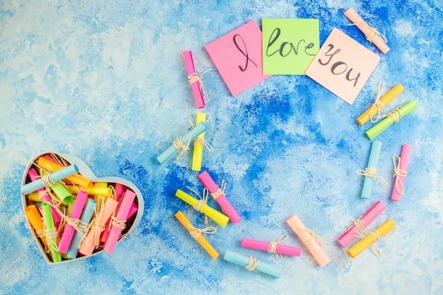 Widok z góry kocham cię napisane na karteczkach samoprzylepnych przewiń papiery życzeń w pudełku w kształcie serca na niebieskim tle kopiuj miejsce